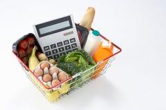 Cesta por completo de tiendas de comestibles y de calculadora Imagen de archivo