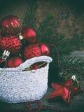 Cesta redonda del ganchillo blanco con las decoraciones rojas de la Navidad en fondo de madera Fondo de la tarjeta del Año Nuevo  Fotografía de archivo libre de regalías