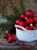 Cesta redonda del ganchillo blanco con las decoraciones rojas de la Navidad en fondo de madera Fondo de la tarjeta del Año Nuevo  Imagenes de archivo