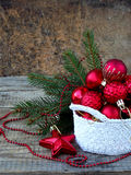 Cesta redonda del ganchillo blanco con las decoraciones rojas de la Navidad en fondo de madera Fondo de la tarjeta del Año Nuevo  Imágenes de archivo libres de regalías