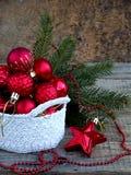 Cesta redonda del ganchillo blanco con las decoraciones rojas de la Navidad en fondo de madera Fondo de la tarjeta del Año Nuevo  Fotografía de archivo