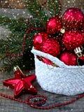 Cesta redonda del ganchillo blanco con las decoraciones rojas de la Navidad en fondo de madera Fondo de la tarjeta del Año Nuevo  Fotos de archivo libres de regalías