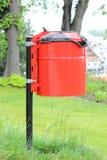 Cesta roja y mojada de la basura en un parque en un fondo de la hierba verde Fotografía de archivo libre de regalías