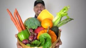 Cesta sonriente de la tenencia del hombre del granjero de frutas y verduras naturales orgánicas frescas almacen de metraje de vídeo