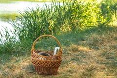 Cesta tejida de la vid, en las orillas del lago en la hierba verde con los platos para una comida campestre, en el día claro del  Imagen de archivo