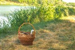 Cesta tejida de la vid, en las orillas del lago en la hierba verde con los platos para una comida campestre, en el día claro del  Fotos de archivo libres de regalías