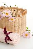 Cesta tejida, toalla rodada y anémonas Foto de archivo