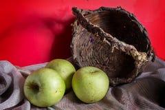 Cesta vieja con las manzanas verdes. Fotos de archivo