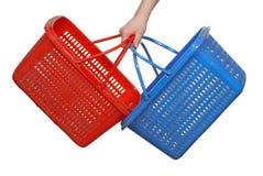 Cestas azul marino y rojas para los productos en una mano, en un CCB blanco Imágenes de archivo libres de regalías