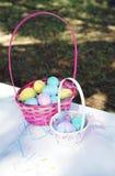 Cestas cor-de-rosa enchidas com os ovos da páscoa fotografia de stock royalty free
