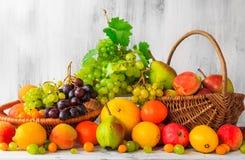Cestas de fruta fresca llenas de la tabla de madera Fotos de archivo