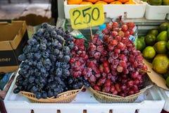 Cestas de fruta de uvas negras y rojas dulces frescas que venden en mercado local con el precio foto de archivo