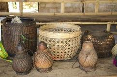 Cestas de mimbre y jarros para el agua en una tabla de madera fotografía de archivo