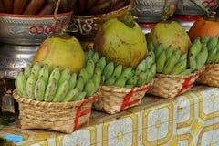 Cestas de plátanos y de cocos verdes Imagen de archivo