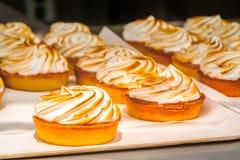 Cestas dos bolos com a merengue apresentada para a venda em um café fotos de stock