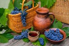 Cestas e bacia com uvas O frasco e o copo com vinho estão sobre na madeira rústica imagem de stock
