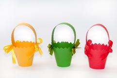 Cestas rojas, verdes y amarillas del cartón para los huevos de Pascua Fotos de archivo libres de regalías