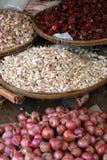 Cestini di aglio, dei peperoncini rossi e delle cipolle. Fotografia Stock