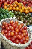 Cestino dei pomodori su una stalla del mercato fotografia stock