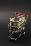 Cestino della spesa con la pila di condizione interna delle banconote in dollari dell'americano cento dei soldi sul fondo nero Immagini Stock Libere da Diritti