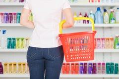 Cestino della spesa di trasporto della donna al supermercato Fotografie Stock Libere da Diritti