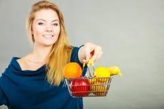 Cestino della spesa della tenuta della donna con i frutti dentro Immagine Stock Libera da Diritti