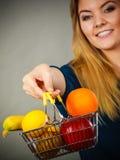 Cestino della spesa della tenuta della donna con i frutti dentro Fotografia Stock Libera da Diritti
