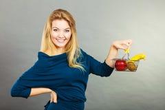 Cestino della spesa della tenuta della donna con i frutti dentro Immagine Stock