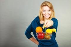 Cestino della spesa della tenuta della donna con i frutti dentro Immagini Stock