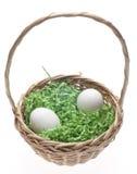 Cestino di Pasqua con erba e due uova bianche Fotografia Stock Libera da Diritti