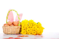 Cestino di Pasqua con le uova, i fiori e le orecchie del coniglietto Fotografia Stock