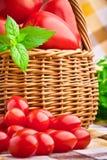 Cestino in pieno dei pomodori freschi e dei pomodori di ciliegia Immagine Stock