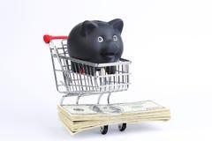 Cesto de compras com mealheiro e a pilha pretos de notas de dólar do americano cem do dinheiro no fundo branco Fotos de Stock Royalty Free