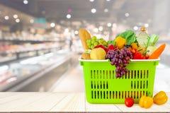 Cesto de compras enchido com as frutas e legumes na tabela de madeira com mercearia do supermercado fotografia de stock royalty free