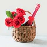 Cesto del regalo del día de tarjeta del día de San Valentín, ramo de rosas rojas, champán en blanco fotografía de archivo