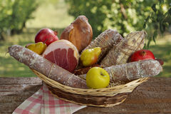 Cesto di salumi in campagna. Basket of cured meats and fruits over to a board. Setting in the countryside Royalty Free Stock Photos