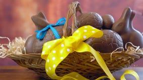 Cesto feliz de Pascua, apilando los huevos de chocolate y los conejos de conejito en cesta grande