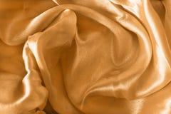 Cetim dourado drapejado imagem de stock royalty free