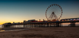 Cetral Pier Dusk. Night begins to fall and the neon lights are on illuminating the ferris wheel and other rides on central pier, blackpool , england Royalty Free Stock Photos