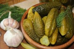 Cetrioli in ciotola di legno, spezie per la marinatura e barattoli dei cetrioli marinati sulla tavola Immagine Stock