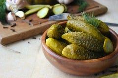 Cetrioli in ciotola di legno, spezie per la marinatura e barattoli dei cetrioli marinati sulla tavola Immagini Stock