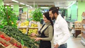 Cetrioli d'acquisto delle coppie felici alla drogheria o al supermercato stock footage