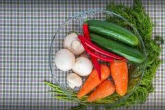 Cetrioli freschi, funghi, peperoncino, carote, verdi su una ciotola trasparente rotonda Immagini Stock