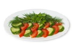 Cetrioli, pomodori e verdi finemente tritati sul piatto Fotografia Stock