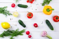 Cetrioli, ravanello, pomodori ciliegia, olio d'oliva, erba e spezie su vecchio fondo di legno bianco Metta per gli alimenti sani  Fotografie Stock