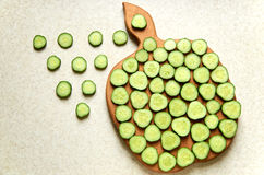 Cetrioli su un bordo di legno della mela di taglio Immagine Stock