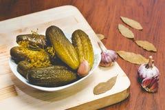 Cetrioli verdi marinati in un piatto bianco, in un aglio fresco e nelle spezie su un bordo di legno immagine stock libera da diritti