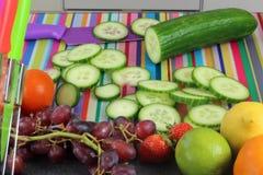 Cetriolo affettato sul tagliere variopinto in cucina Fotografia Stock