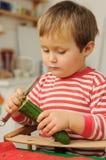 Cetriolo della sbucciatura del bambino in giovane età Fotografia Stock