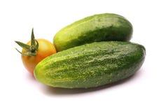 Cetriolo e pomodoro su una priorità bassa bianca Fotografia Stock